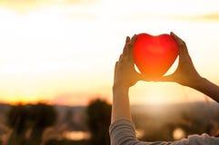 Schattenbild von den Händen, die rote Herzen über bewölktem Himmel halten Stockfoto