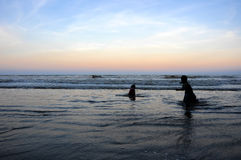 Schattenbild von den Jungen, die am Strand während des Sonnenuntergangs spielen Lizenzfreies Stockbild