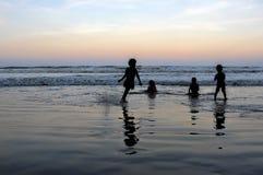Schattenbild von den Jungen, die am Strand während des Sonnenuntergangs spielen Stockbild