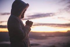Schattenbild von den jungen menschlichen Händen, die zum Gott bei Sonnenaufgang, Christian Religions-Konzepthintergrund beten stockfoto