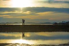 Schattenbild von den jungen romantischen Paaren, die mit dem kleinen Baby des Sohns oder der Tochter genießt den Sonnenuntergang  lizenzfreies stockbild