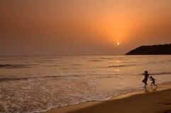 Schattenbild von den Kindern, die auf dem Strand spielen Lizenzfreies Stockfoto