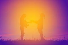 Schattenbild von den Kindern, die Geschenkbox bei dem Himmelsonnenuntergang halten Stockbild