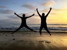 Schattenbild von den Leuten, die bei Sonnenuntergang auf einem Strand springen Stockbild