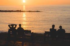 Schattenbild von den Leuten, die Sonnenuntergang genießen Lizenzfreie Stockfotos