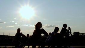 Schattenbild von den Leuten, die Yoga das im Freientun - Meditation und Sportkonzept für gesunden und entspannenden Lebensstil -  stock video