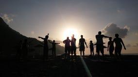 Schattenbild von den Leuten, die Yoga zur Seeküsten-Sonnenaufgangzeit tun Stockfotos