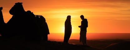 Schattenbild von den Männern, die in der Wüste bei Sonnenuntergang stehen stockbilder