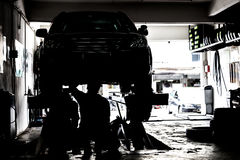 Schattenbild von den Mechanikern, die Autos an einer kleinen Werkstatt instandhalten Lizenzfreie Stockfotografie