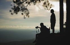 Schattenbild von den Reisenden, die einen schönen Bergblick genießen Stockbild