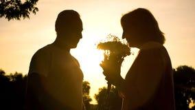 Schattenbild von den riechenden Blumen der Frau dargestellt vom Mann, Jahrestag feiernd lizenzfreies stockbild