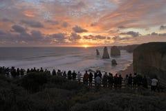 Schattenbild von den Touristen, welche die zw?lf Apostel-gro?e Ozean-Stra?e in Victoria Australia betrachten stockbild
