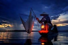 Schattenbild von den traditionellen Fischern, die Nettofischensee im mystischen clound bei Sonnenuntergang werfen Lizenzfreie Stockfotos