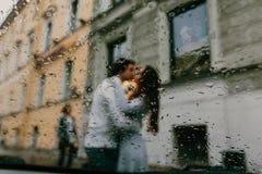 Schattenbild von den unscharfen Liebhabern, die auf der Straße der Stadt küssen Ansicht vom Fenster eines Autos oder des Cafés Lizenzfreies Stockbild