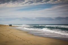 Schattenbild von drei Abbildungen auf dem Strand Stockbild