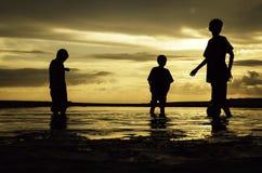 Schattenbild von drei Jungen, die mit dem Ball auf dem Strand bei während Sonnenaufgang spielen Stockbilder