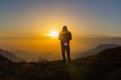 Schattenbild von einem jungen Mann, der an der Gebirgsspitze steht Stockbild