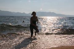 Schattenbild von einem Mädchen, das durch die Wellen läuft Lizenzfreie Stockbilder