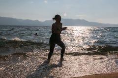 Schattenbild von einem Mädchen, das durch die Wellen läuft Stockfotografie