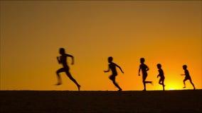 Schattenbild von fünf laufenden Kindern gegen Sonnenuntergang