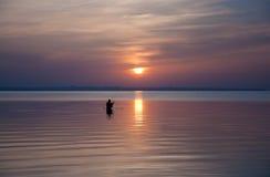 Schattenbild von Fischern auf einem Sonnenunterganghintergrund Stockbild