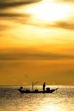 Schattenbild von Fischern im Boot auf Meer mit gelber und orange Sonne im Hintergrund lizenzfreie stockfotografie