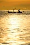 Schattenbild von Fischern im Boot auf Meer mit gelber und orange Sonne im Hintergrund lizenzfreie stockbilder