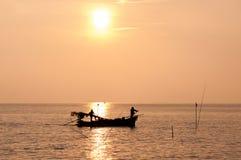 Schattenbild von Fischern mit gelber und orange Sonne im Hintergrund stockfotografie