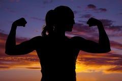 Schattenbild von Fraueneignungsflex, das beide Arme schließen lizenzfreie stockbilder