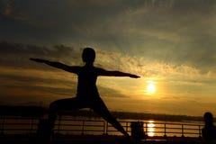 Schattenbild von Frauenzug Yoga auf Rasenyard entlang Fluss-Berg lizenzfreie stockbilder