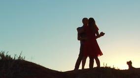 Schattenbild von glücklichen jungen langsamen bei Sonnenuntergang draußen tanzen des verheirateten Paars und des Hundes Zeitlupev stock video