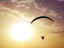 Schattenbild von Gleitschirmfliegen mit Sonnenunterganghintergrund Stockbild