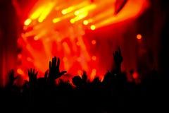 Schattenbild von Händen in der Luft auf einem Konzert stockfotografie