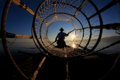 Schattenbild von intha Fischer gegen den Sonnenunterganghimmel Stockbild