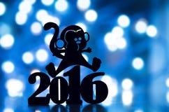 Schattenbild von 2016-jährigem und von Affen mit blauer Girlande beleuchtet auf b Stockfotografie