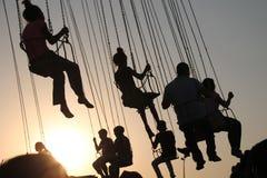 Schattenbild von jungen Leuten auf Riesenrad und schwingkarussell in der Endbewegung auf Sonnenunterganghintergrund stockfoto