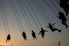 Schattenbild von jungen Leuten auf Riesenrad und schwingkarussell in der Endbewegung auf Sonnenunterganghintergrund stockfotografie
