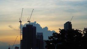 Schattenbild von Kränen und Wolkenkratzern bei wunderbarem Sonnenuntergang von konstruieren Errichten in der Großstadt stock footage
