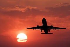 Schattenbild von Landungsflugzeugen und von rotem Himmel mit Sonne Lizenzfreie Stockfotografie