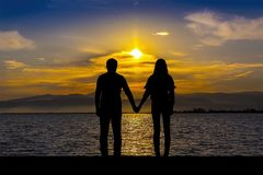 Schattenbild von Männern und von Frauen, die Hände halten, auf der Küste bei Sonnenuntergang Stockfoto