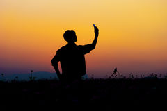 Schattenbild von Mann selfie Schattenbild des Mannes aufwerfend bei Sonnenuntergang Stockbild