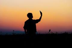 Schattenbild von Mann selfie Schattenbild des Mannes aufwerfend am Sonnenunterganghimmel Stockfotografie
