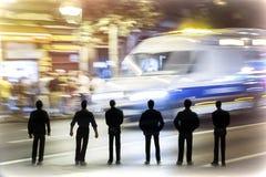 Schattenbild von mehreren bemannen das Betrachten eines Krankenwagens mit voller Geschwindigkeit während der Nacht Lizenzfreie Stockfotos