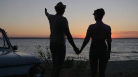 Schattenbild von Paaren die Händchenhalten und Blicke im Abendsonnenuntergang draußen, romantische Reise von Liebhabern zur Seese stock footage