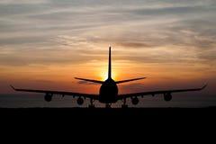 Schattenbild von Passagierflugzeugen, Fluglinie auf schönem Sonnenuntergang Lizenzfreie Stockfotografie
