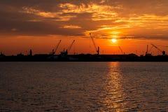 Schattenbild von Seehafenkränen bei Sonnenaufgang Chioggia, Italien Stockfoto