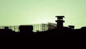 Schattenbild von Stacheldrähten und von Wachturm des Gefängnisses Lizenzfreie Stockfotos