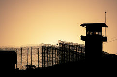 Schattenbild von Stacheldrähten und von Wachturm des Gefängnisses Stockfotos