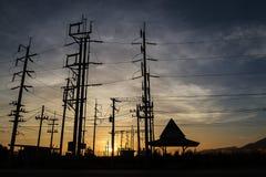 Schattenbild von Strombeiträgen während des goldenen Sonnenuntergangs Stockfotos