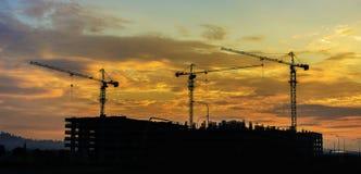 Schattenbild von Turmkranen während des Sonnenuntergangs Lizenzfreies Stockfoto